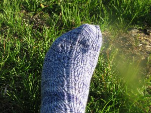 Blue and white yarn in the form of a mermaid tail sock.